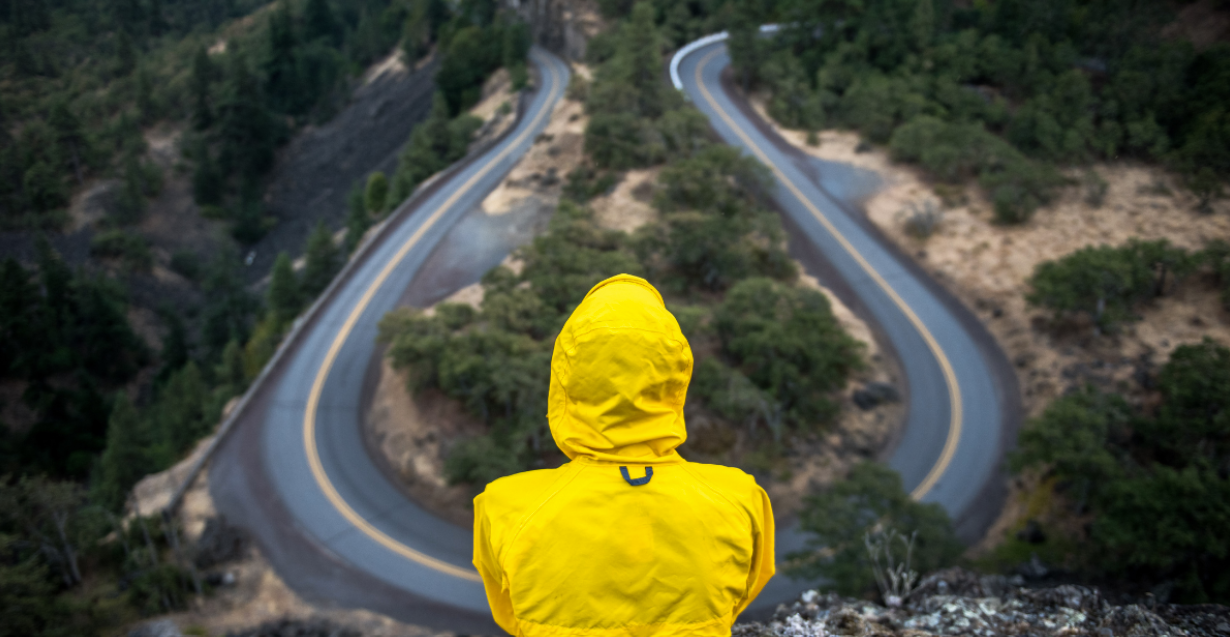 Person in yellow rain jacket looking at road